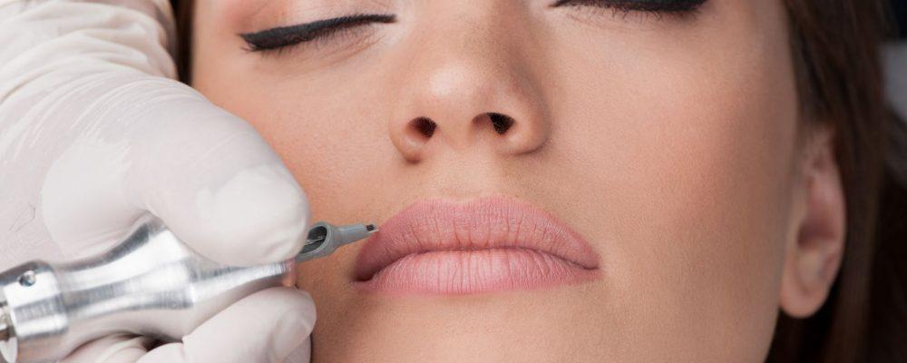 27044233 - beautiful young girl getting tattoo. professional tattooist making permanent make up