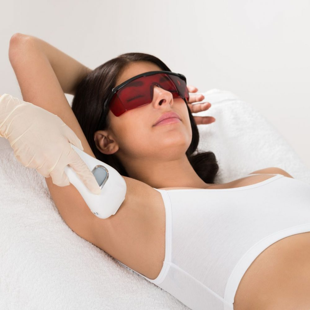 39657489 - woman receiving epilation laser treatment on armpit at beauty clinic
