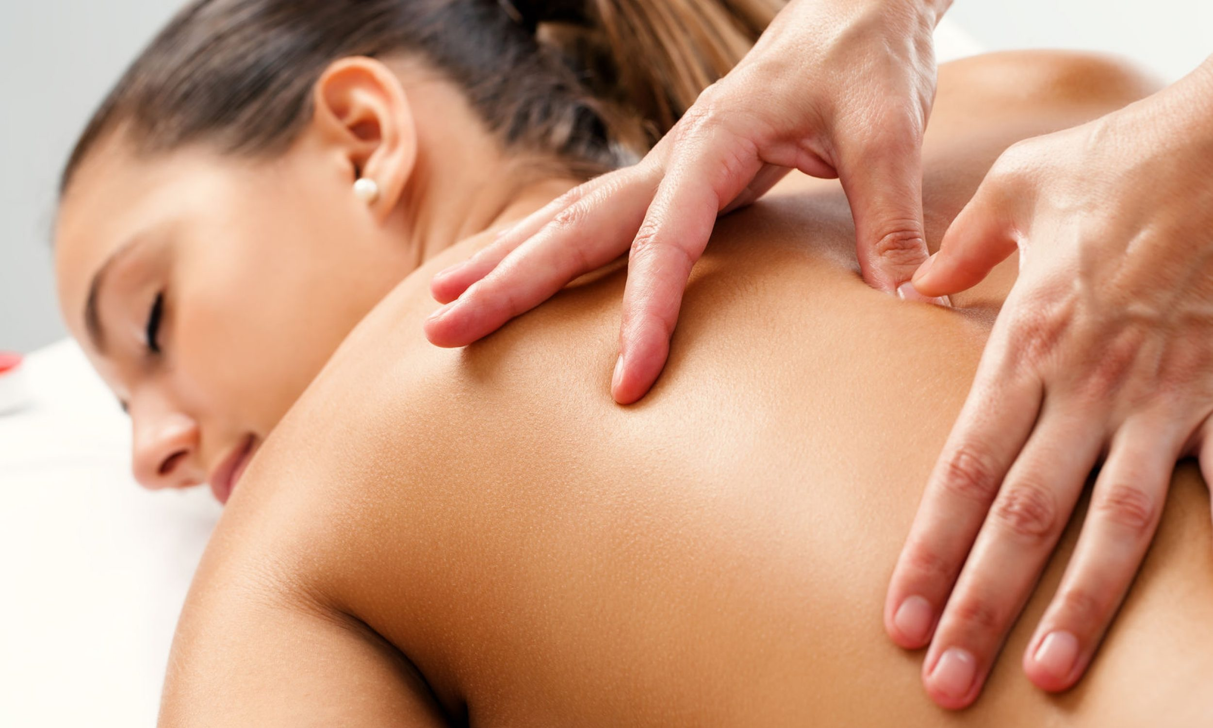 45232073 - close up of therapist doing curative healing massage with thumbs on female back.
